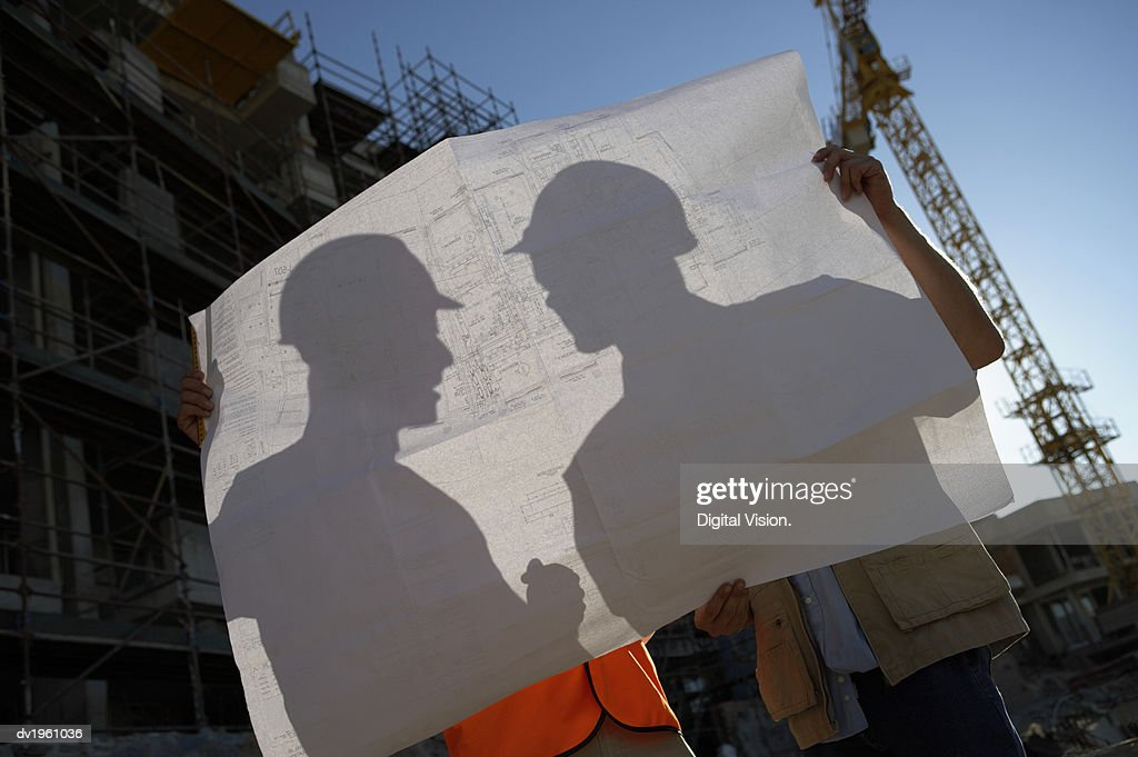 Two Builders Silhouetted Through Blueprints : Stock Photo