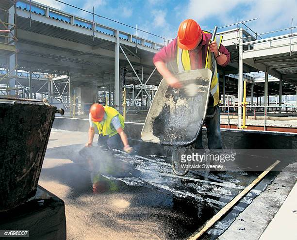 two builders spreading tar over a rooftop - tar stock pictures, royalty-free photos & images