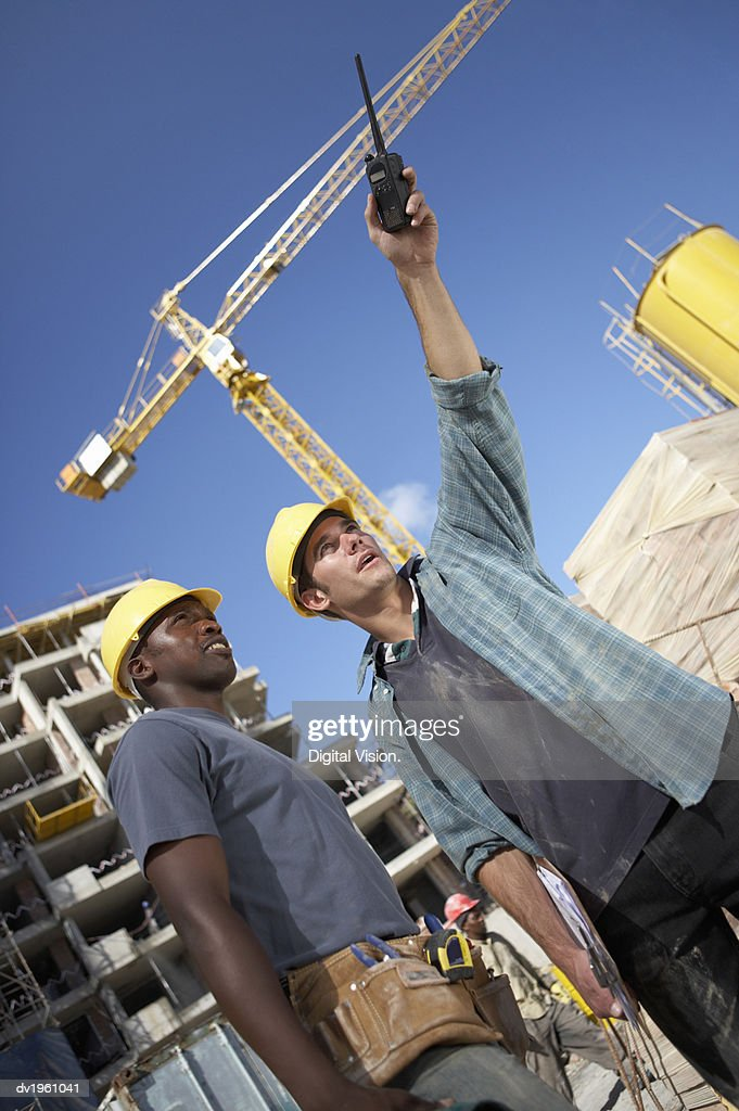 Two Builders Working on a Building Site, with One Man Pointing with a Walkie Talkie : Stock Photo