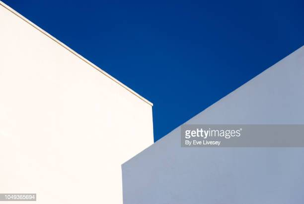 two buildings and a blue sky - blanco color fotografías e imágenes de stock