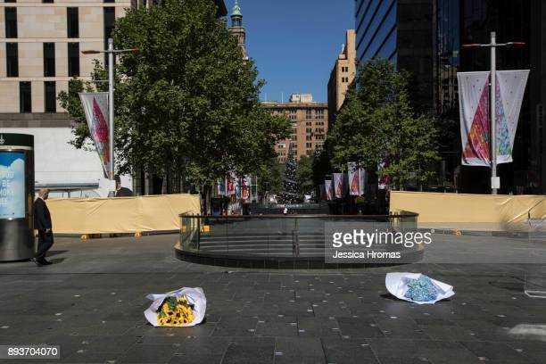 Two bunches of flowers lay on the ground at the site of a permanent memorial honouring the lives of Tori Johnson and Katrina Dawson at Martin Place...