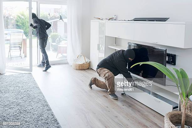 two burglars at work in an one-family house at daytime - burglar stock pictures, royalty-free photos & images