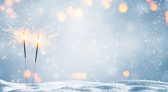 two burning sparklers in snow 1050730046