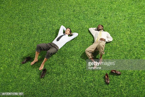 Two busienss men lying on grass, elevated view