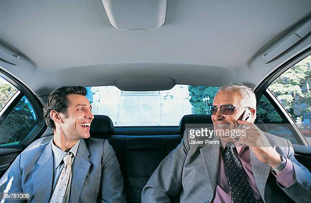 Two Businesmen Dressed in Full Suits Sitting in the Back Seat of a Car