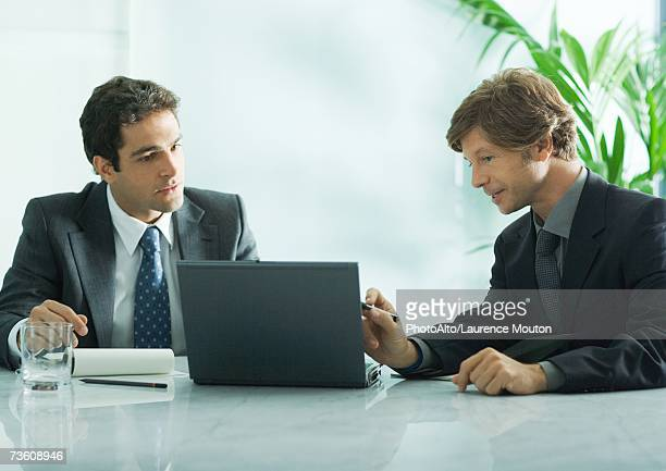 Two businesmen sitting at table, looking at laptop