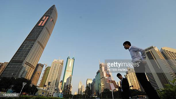 Two businesmen talk between skyscrapers in the southern Chinese city of Shenzhen in the province of Guangdong on November 30 2011 Shenzhen once a...