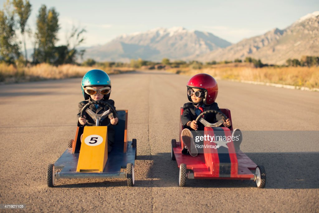Two Business Boys Sit in Toy Cars on Street : Stock Photo