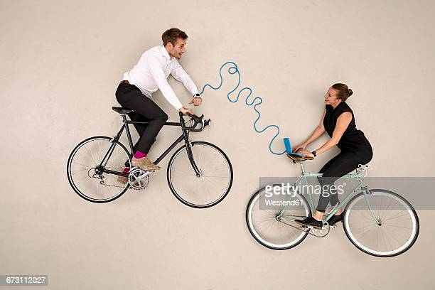 Two business colleagues biking and communicating via laptop and smartwatch