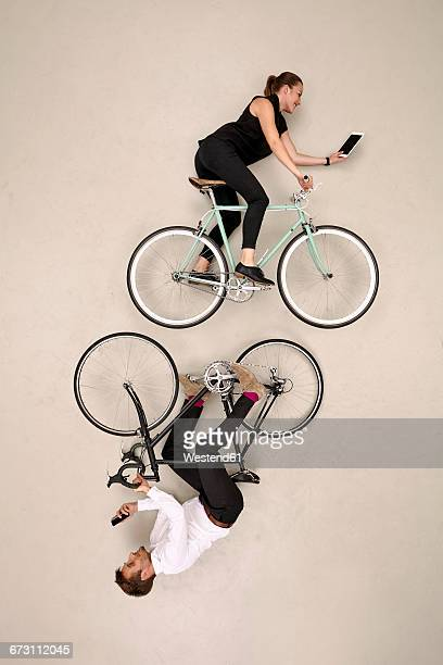 Two business colleagues biking with smartphone and tablet, mirroring each other