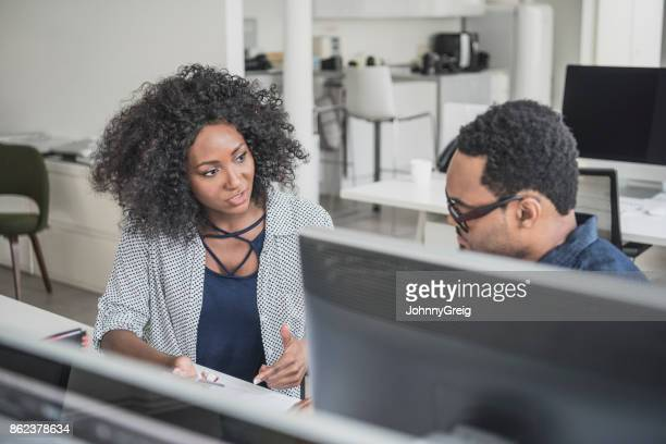 Two business colleagues discussing at desk with woman explaining to man
