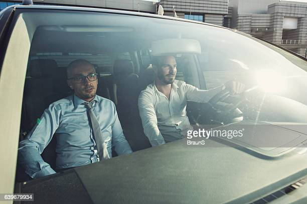 Two business colleagues going on a trip by car.