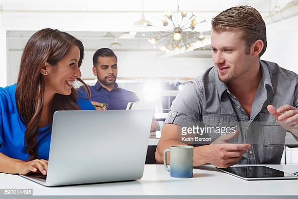 Two business colleagues having discussion at desk