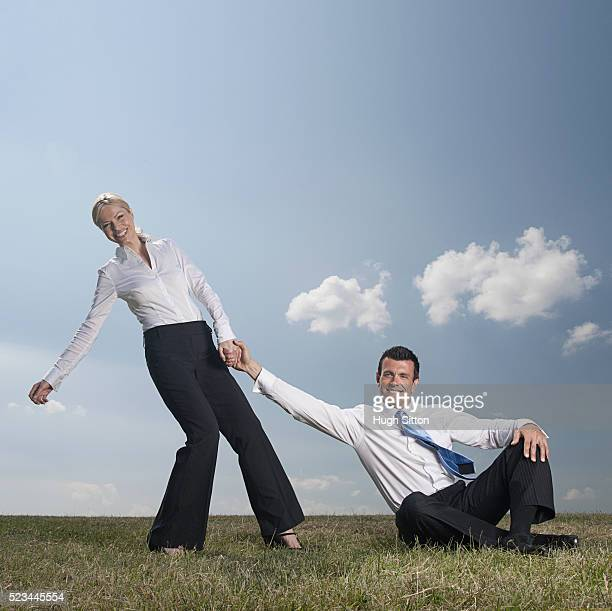 two business colleagues helping each other, outdoors - hugh sitton stock pictures, royalty-free photos & images