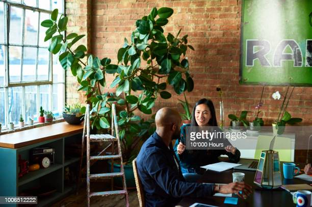 two business colleagues in modern office discussing work - studio workplace stock pictures, royalty-free photos & images