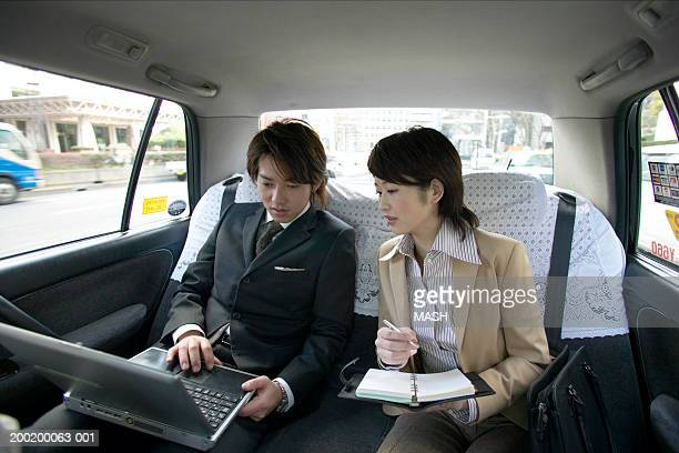 Two business colleagues in taxi, looking at laptop screen, interior view
