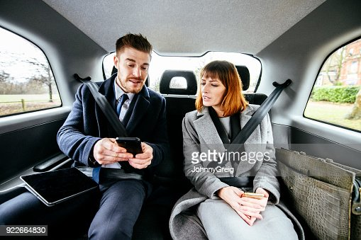 Two business colleagues in taxi with smartphone and tablet