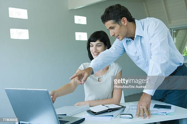 Two business colleagues looking at computer monitor, pointing to screen