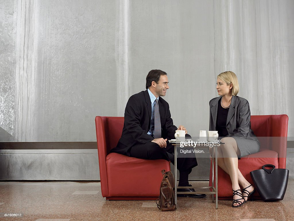 Two Business Colleagues Sit Face-To-Face on Chairs at a Coffee Table : Stock Photo
