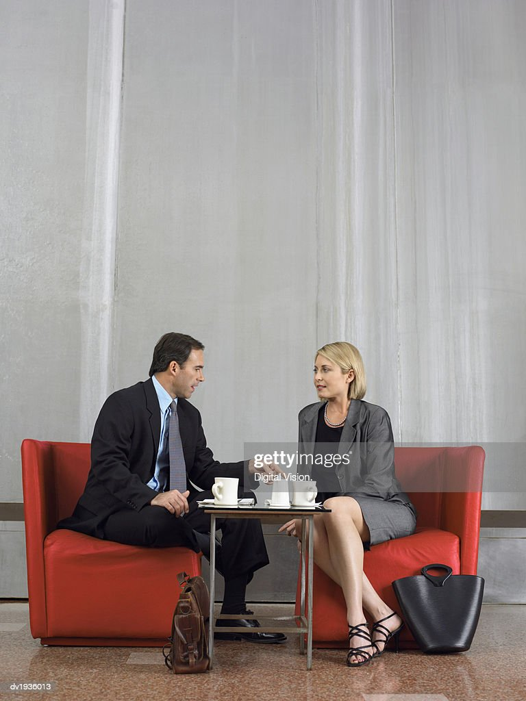 Two Business Colleagues Sit Talking on Chairs at a Coffee Table : Stock Photo