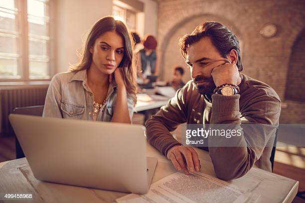 Two business colleagues working together on a laptop at office.