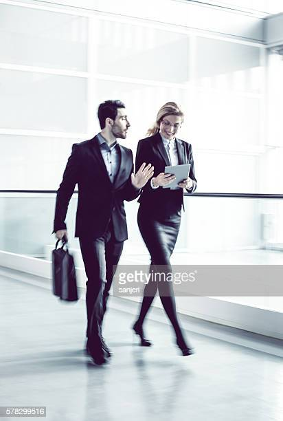 Two Business coworkers walking along office coridor