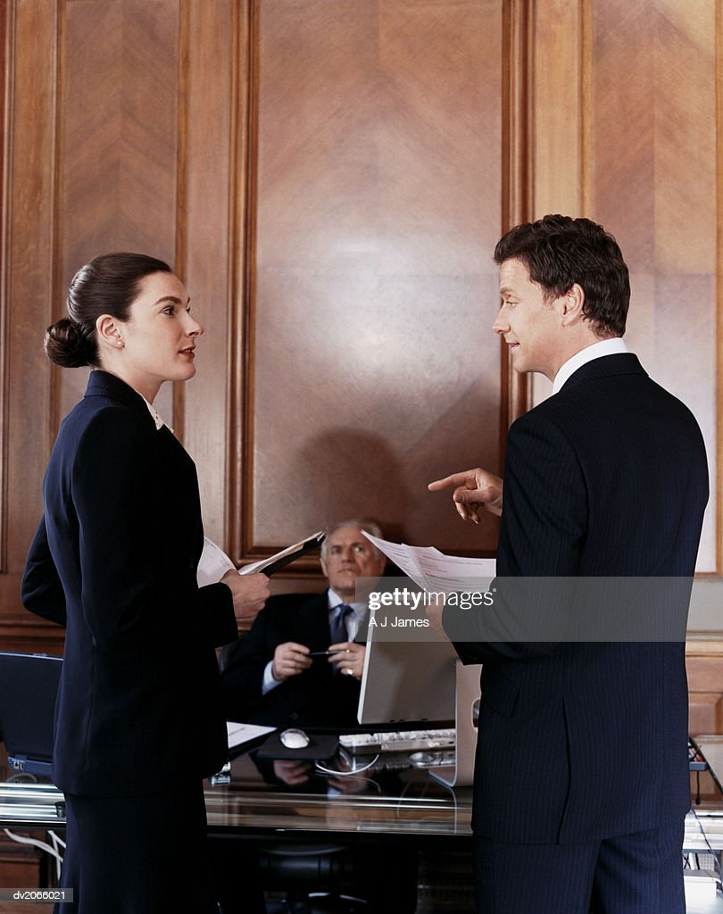 Two Business Executives Having a Discussion in Front of the CEO's Desk : Stock Photo