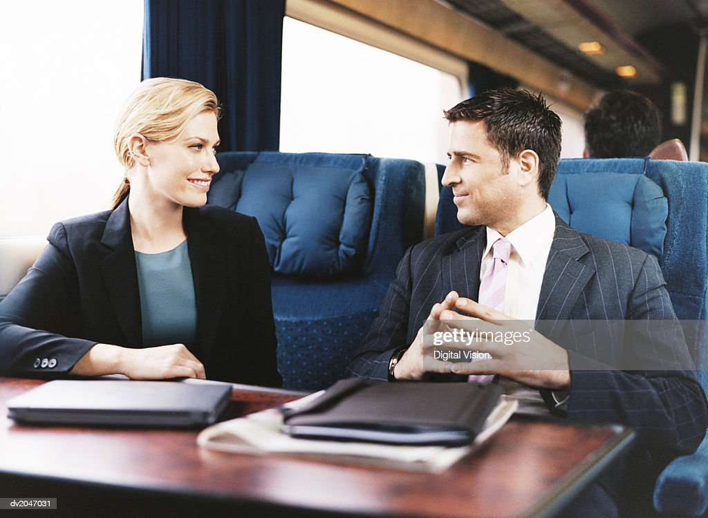 Two Business Executives Looking at Each Other Face to Face on a Passenger Train : Stock Photo