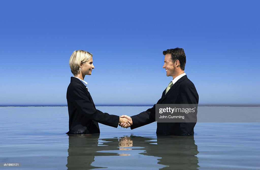 Two Business Executives Shaking Hands and Standing in the Sea : Stock Photo
