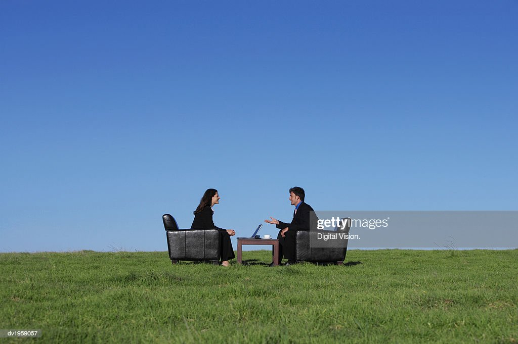 Two Business Executives Sitting in Armchairs on the Grass Talking to One Another : Stock Photo