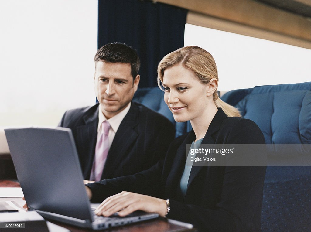 Two Business Executives Sitting on a Passenger Train and Working on a Laptop : Stock Photo