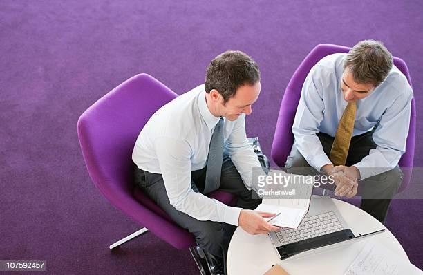 dois empresários sentado com laptop a discutir no relatório - color lavanda - fotografias e filmes do acervo