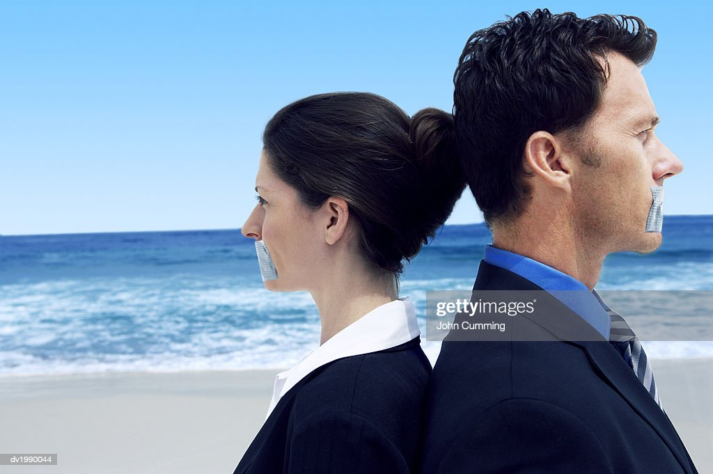 Two Business Executives Standing Back to Back on a Beach With Their Mouths Covered by Duct Tape : Stock Photo