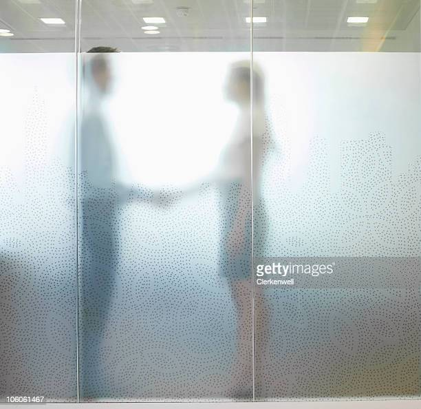 Two business executives standing behind glass door