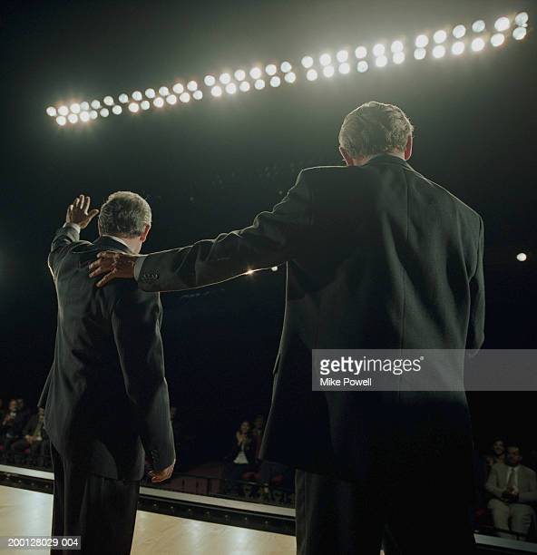 Two Business executives standing on stage, one waving at crowd
