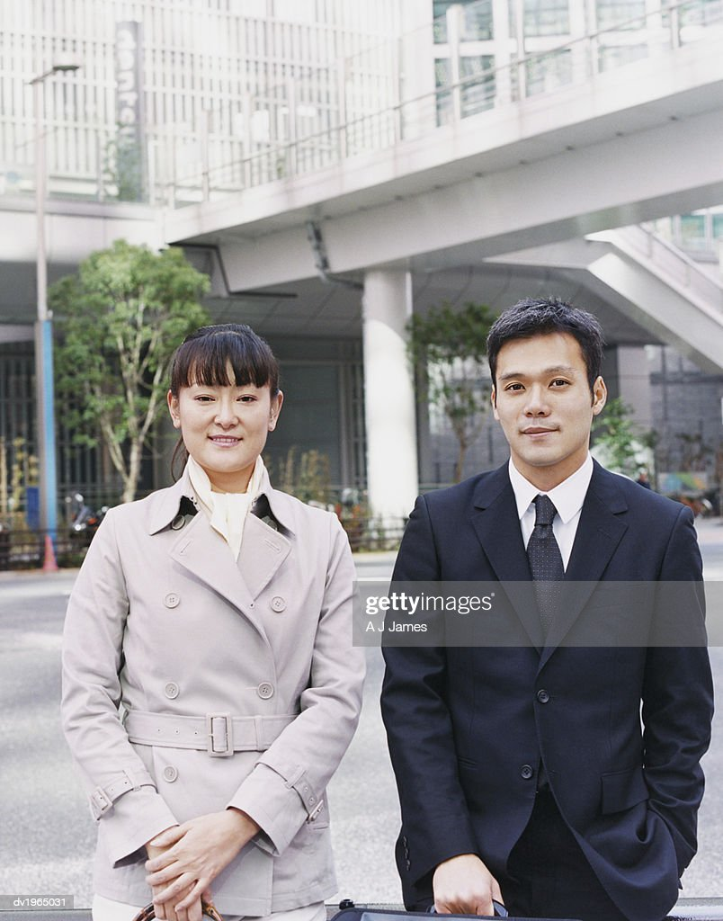Two Business Executives Standing Side by Side, with a Footbridge in the Background : Stock Photo
