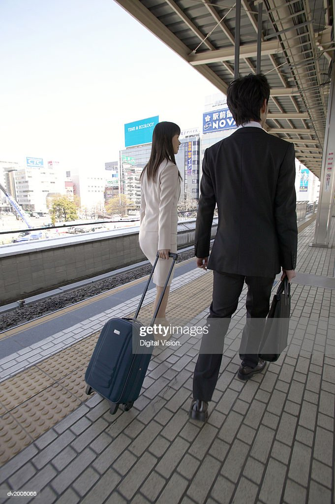 Two Business Executives Walking on a Train Platform : Stock Photo