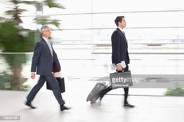 Two business executives with luggage, side view