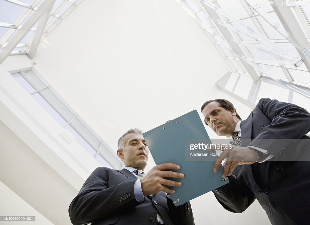 Two business men holding clipboard, discussing, directly below : Stockfoto