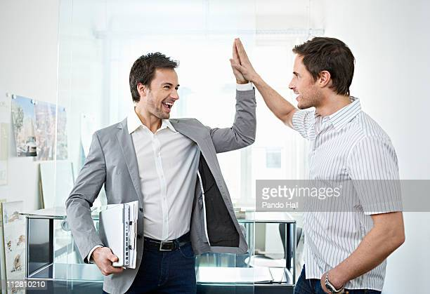 Two business men in office cheering