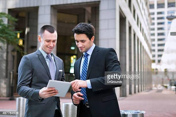 Zwei Geschäftsleute, die auf Nachrichten auf tablet-PC
