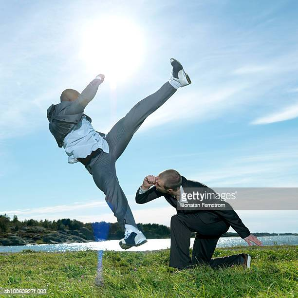 two business men performing capoiera on a field by the sea, side view - 足を開く ストックフォトと画像