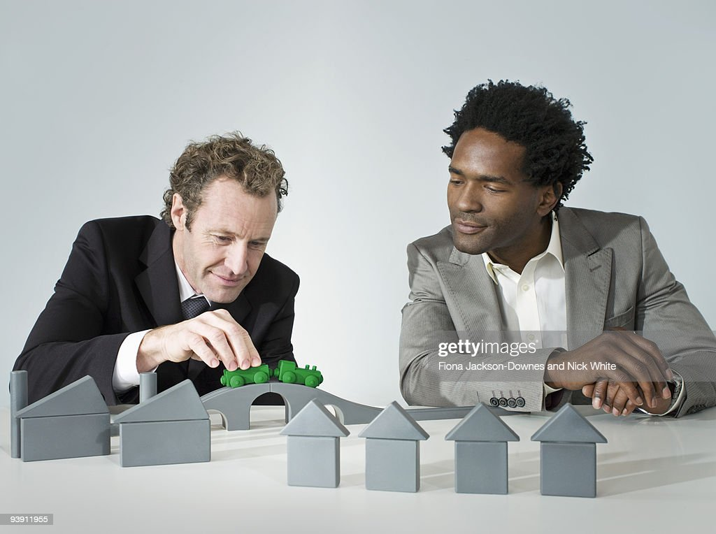 Two business men play with a train : Photo