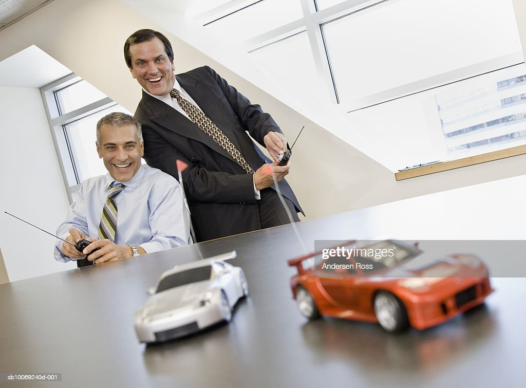 Two business men playing with remote control cars : Stockfoto