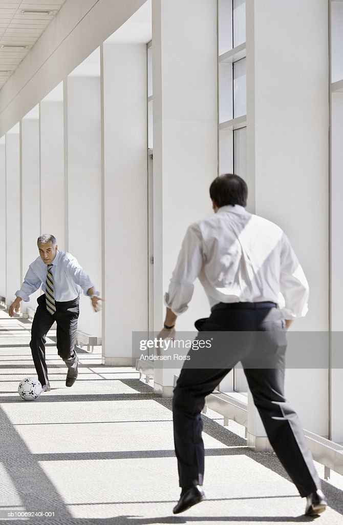 Two business men playing with soccer ball in office : Stockfoto