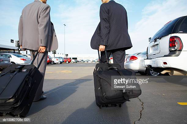 Two business men pulling suitcases through car rental lot, rear view
