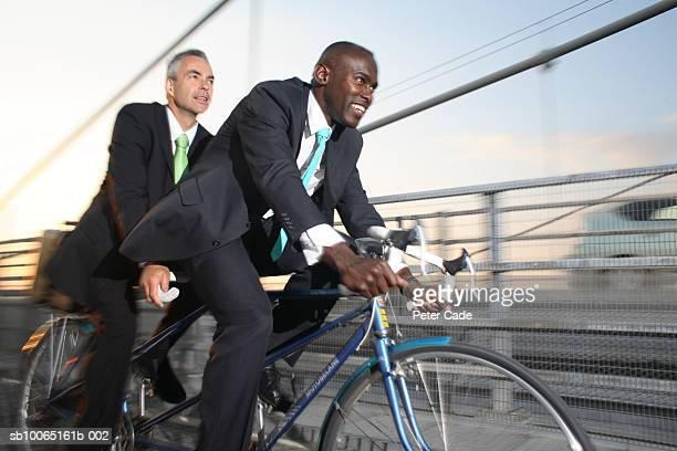 Two business men riding on tandem bike on bridge