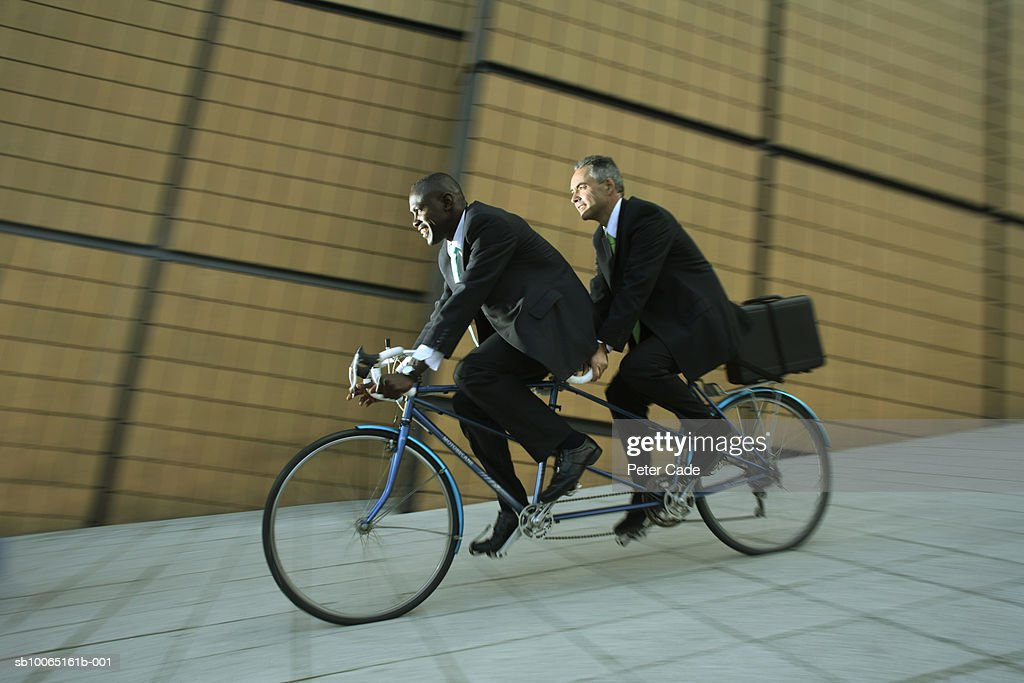 Two Business Men Riding On Tandem Bike Side View Stock Photo | Getty