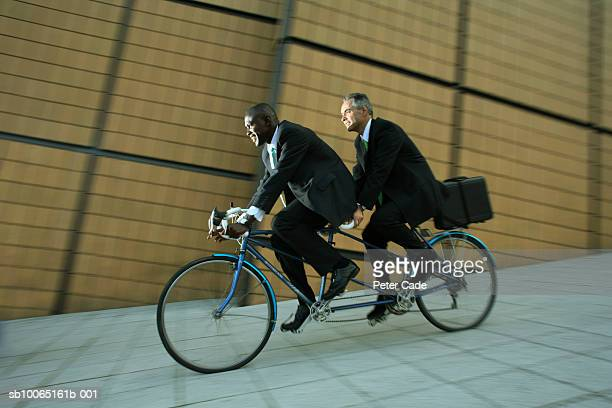Two business men riding on tandem bike, side view