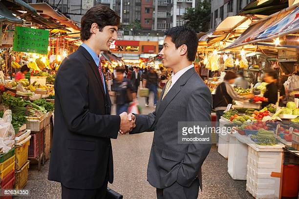 Two business men shaking hands at street market